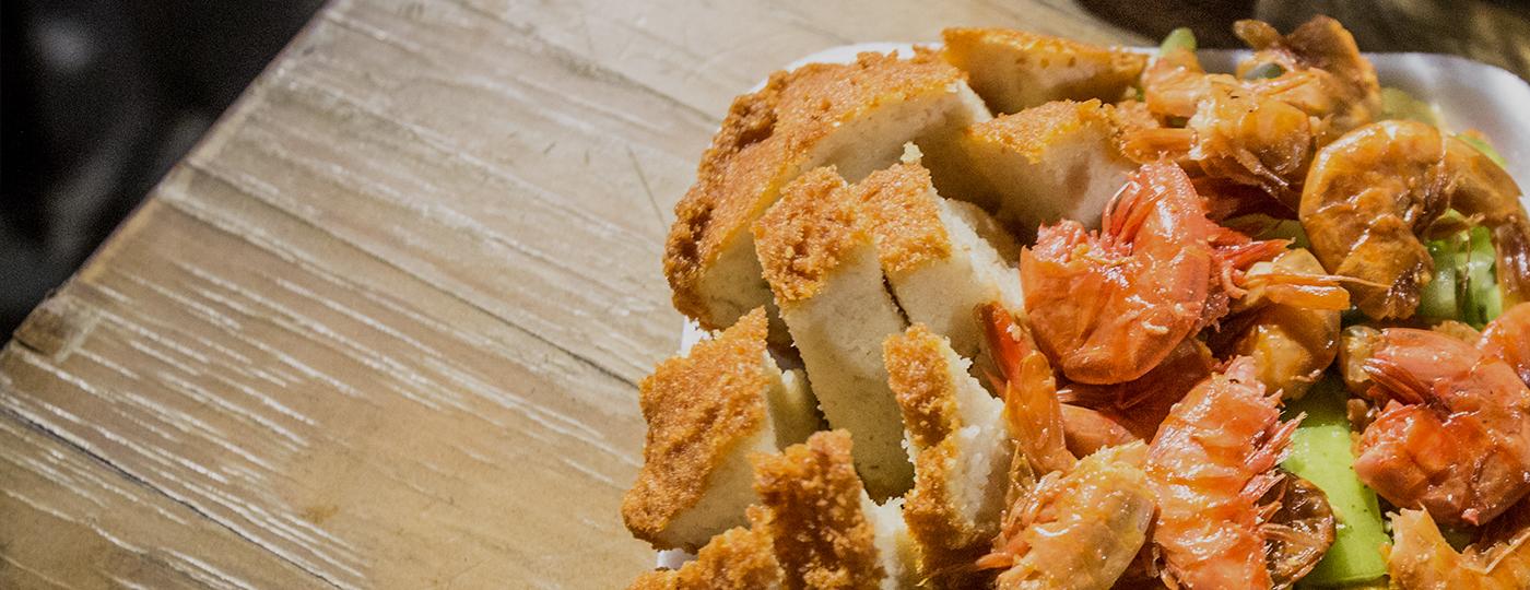 Comidas típicas do Nordeste: prato com acarajé e vatapá sobre uma mesa de madeira.