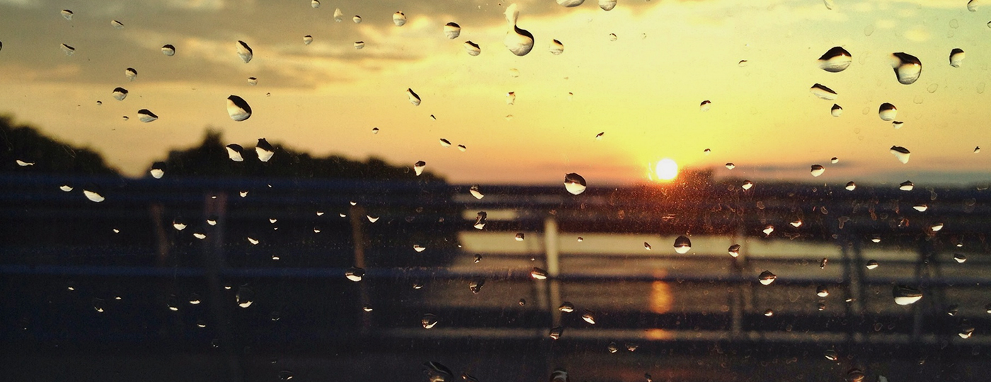 Janela molhada com por do sol de fundo
