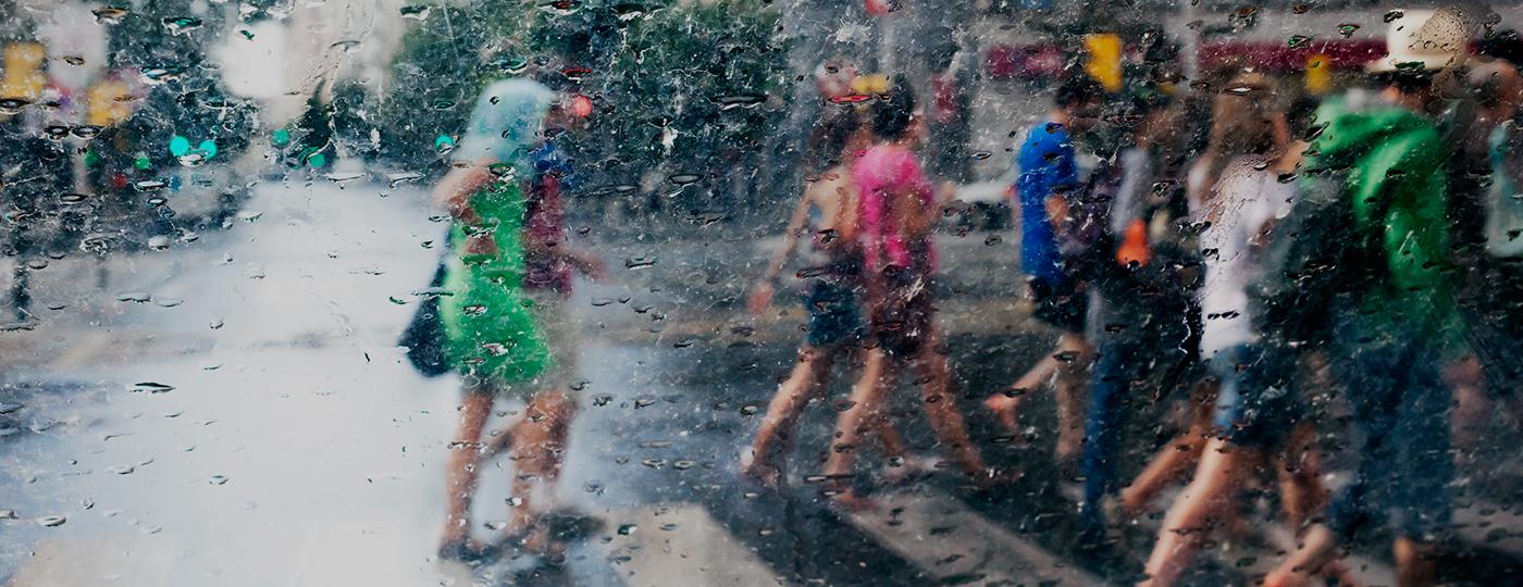 Pessoas atravessando a rua com chuva